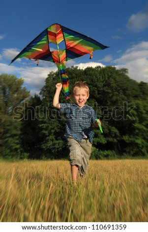 Happy boy  with bright kite running across the field - stock photo
