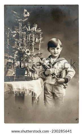 happy boy with christmas tree, gifts and vintage toys. antique sepia picture with original film grain and scratches - stock photo