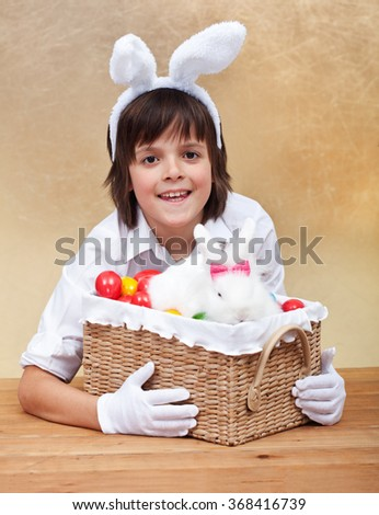 Happy boy with easter basket - holding colorful eggs and cute bunny - stock photo