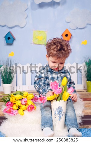Happy boy with flowers. Yellow and pink tulips, March 8, Mother's Day, International Women's Day - stock photo