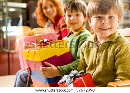 Happy boy with gift in hands sitting in supermarket on background of his brother and mother - stock photo