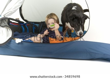 happy boy with hand magnifying glass, bug in tent with his pet dog. camping or outdoor theme - stock photo