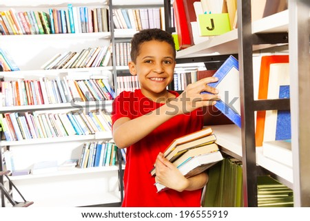 Happy boy with hand on bookshelf holds many books - stock photo