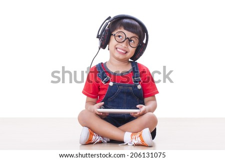 Happy boy with headphones connected to a tablet to listen to music  - stock photo