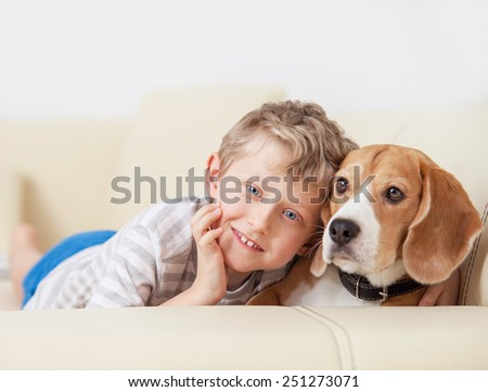 Happy boy with his dog lying on sofa - stock photo