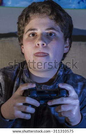 Happy. boy with joystick playing computer game at home. - stock photo