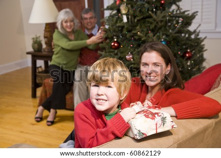 Happy boy with mother and grandparents at Christmas
