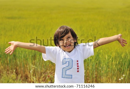 Happy boy with open arms outdoor - stock photo