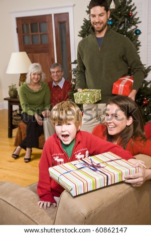 Happy boy with parents and grandparents at Christmas - stock photo