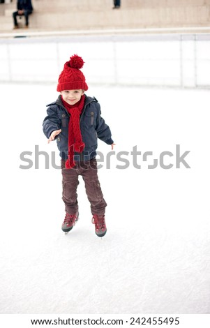 Happy boy with red hat, skating during the day, having fun - stock photo