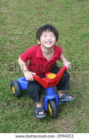 Happy boy with red shirt riding bicycle at the field - stock photo