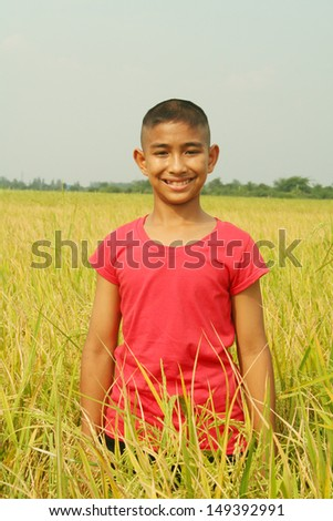Happy boy with rice field background.  - stock photo