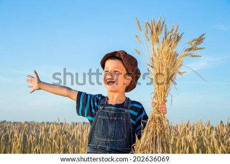 Happy boy with sheaf of wheat on the field - stock photo