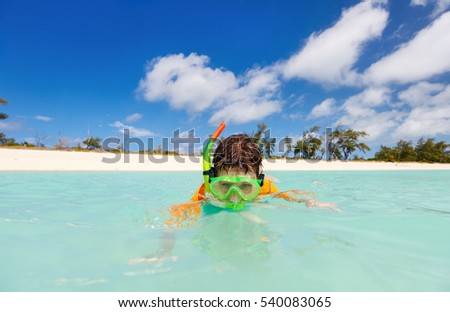 Happy boy with snorkeling mask in turquoise tropical ocean water