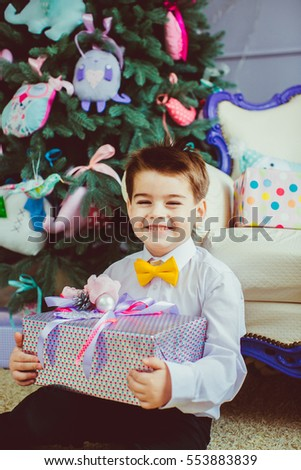 Happy boy with the yellow bow-tie and a gift