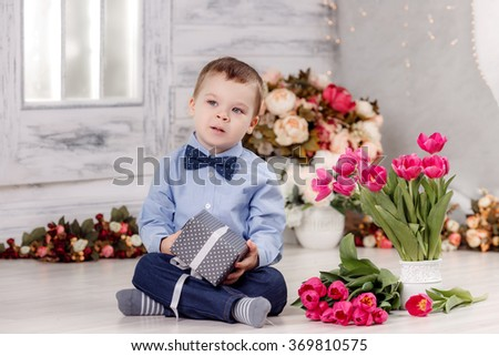 Happy boy with tulips. March 8, Women's Day, Mother's Day - stock photo