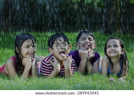 Happy boys and girls catching raindrops on tongue - stock photo
