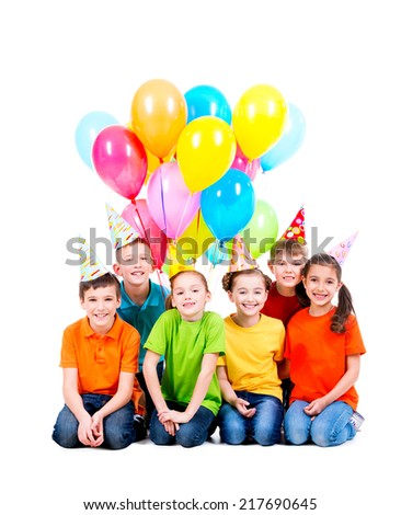 Happy boys and girls in party hat with colored balloons sitting on the floor - isolated on white. - stock photo
