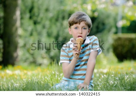 Happy boys eat ice cream on a grass outdoors in spring park - stock photo