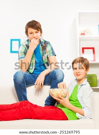 Happy boys eat popcorn while sitting on white sofa - stock photo