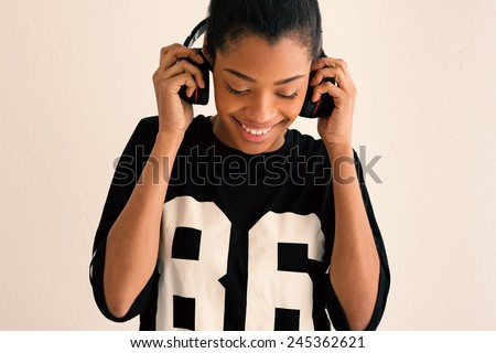Happy brazilian girl portrait with headphones. Filtered image. - stock photo