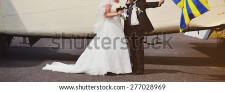 Happy bridal couple against old aircraft.  Wedding picture.