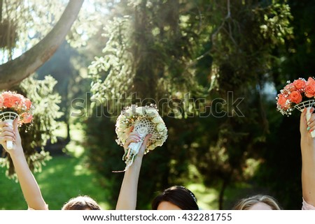 happy bride and bridesmaids showing their luxury bouquets in hands at wedding reception in sunny park - stock photo