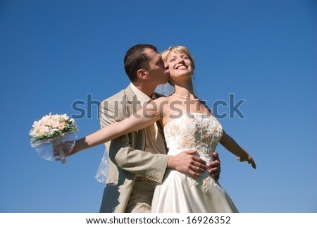 happy bride and groom against blue sky