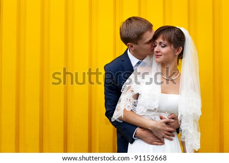 Happy Bride and groom against yellow wall - stock photo