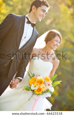 happy bride and groom at a park on their wedding day, focus on bride's face, shallow dof - stock photo