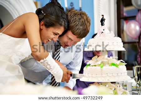 Happy bride and groom cut the wedding cake - stock photo