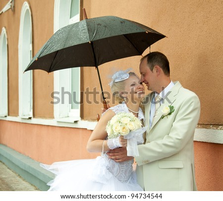 Happy bride and groom embracing under an umbrella - stock photo