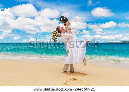 happy bride and groom having fun on a tropical beach - stock photo