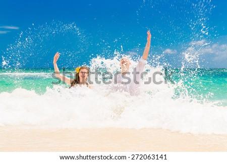 Happy bride and groom having fun on a tropical beach. Wedding and honeymoon on the tropical island. - stock photo