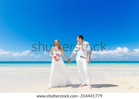 Happy bride and groom having fun on a tropical beach. Wedding and honeymoon on the tropical island.