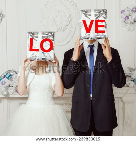 Happy bride and groom holding LOVE. Bride and groom, original wedding. Wedding, love, groom, bride, gift, day, gift box - holiday concept. - stock photo