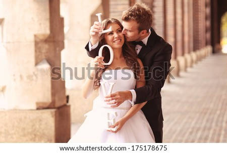 Happy bride and groom holding LOVE letters - stock photo