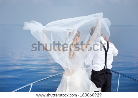 Happy bride and groom hugging on a yacht - stock photo