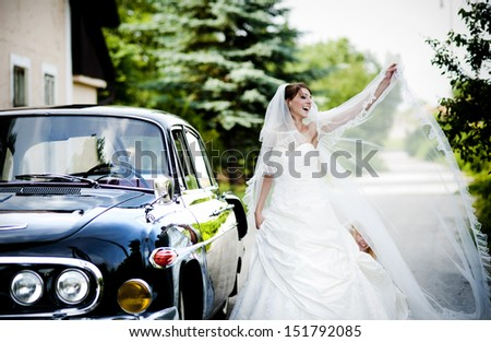 Happy bride and groom in a black car on wedding day - stock photo