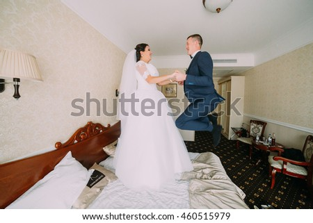 Happy bride and groom in a hotel room playfully jumping on bed. Honeymoon concept