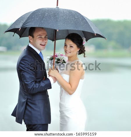 Happy bride and groom in a rainy wedding day hiding from rain