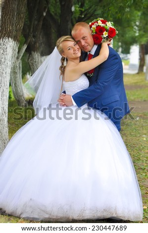Happy bride and groom in the park - stock photo