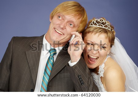 Happy bride and groom is congratulated by phone on blue background - stock photo