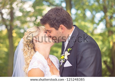 happy bride and groom kissing in the summer forest