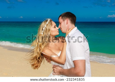 Happy bride and groom kissing on a tropical beach. Blue sea in the background.  Honeymoon. - stock photo