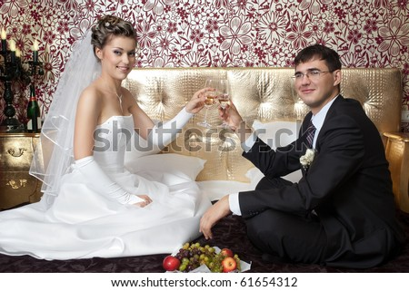 Happy bride and groom making toast on bed in stylish hotel room