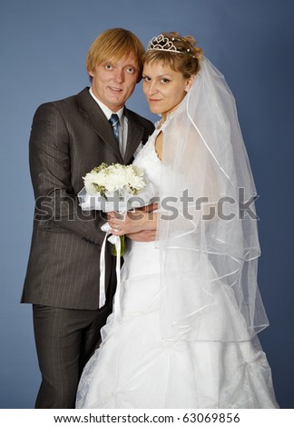 Happy bride and groom on a blue background - stock photo