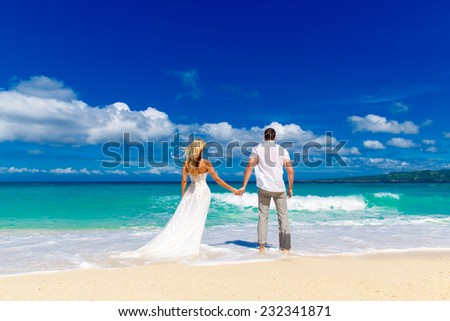 happy bride and groom on a tropical beach - stock photo