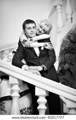 Happy bride and groom on a white ladder on wedding day - stock photo