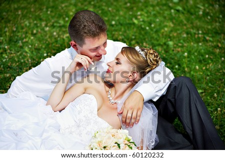Happy bride and groom on grass in park - stock photo